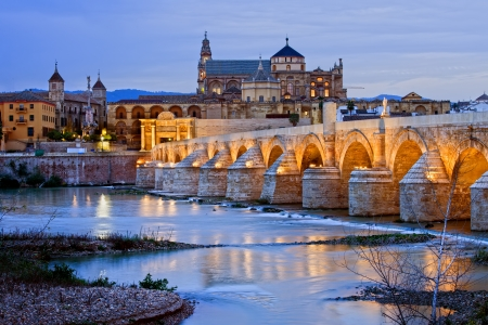 cordoba: Roman Bridge on Guadalquivir river and Mezquita Cathedral (Great Mosque) at dawn in the city of Cordoba, Andalusia, Spain.