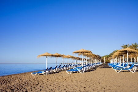 costa: Sun loungers on a tranquil beach at the popular resort city of Marbella in Spain, Costa del Sol, Malaga province.