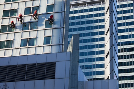 Office buildings abstract modern architecture in the city downtown and window cleaners team at work in Warsaw, Poland.