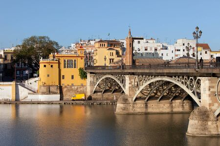 isabel: Triana Bridge (Isabel II Bridge) from 19th century on Guadalquivir river in the city of Seville, Spain. Stock Photo