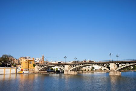 isabel: Triana Bridge (Isabel II Bridge) from 19th century on Guadalquivir river in the city of Seville, Andalusia, Spain. Stock Photo