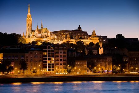 River city view of Budapest at evening in Hungary with illuminated Matthias Church on Buda hill. photo