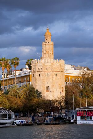 13th century: Torre del Oro (Gold Tower) at sunset by the Guadalquivir river, medieval landmark from early 13th century in Seville, Spain, Andalusia region. Stock Photo