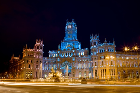 Palacio de Comunicaciones and the Cibeles Fountain on Plaza de Cibeles, illuminated at night in the city of Madrid, Spain.