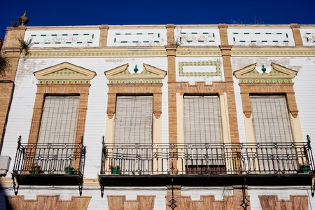 Traditional ornate facade of an Andalusian house with balconies and windows with outdoor roller blinds in Ronda, Andalusia, Spain