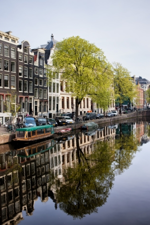 sights: Houses along Singel canal historic waterfront, city of Amsterdam in spring, Holland.