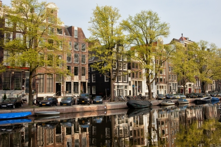 tree linked: Historic houses along the Singel canal in spring, city of Amsterdam, Netherlands.