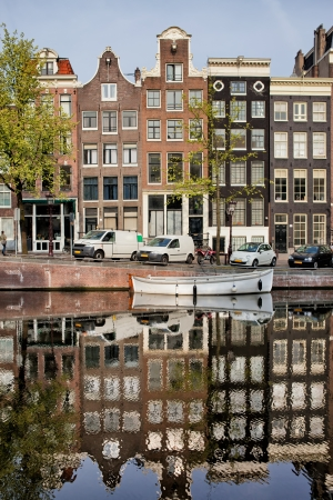 Singel canal historic terraced houses with reflection on water in the city of Amsterdam, Netherlands. photo