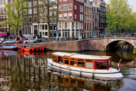 City of Amsterdam in Holland picturesque scenery, boats on a canal and historic terraced houses. photo