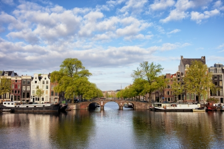 amstel river: Dutch houses and bridge by the Amstel river in Amsterdam, Netherlands, North Holland province. Stock Photo