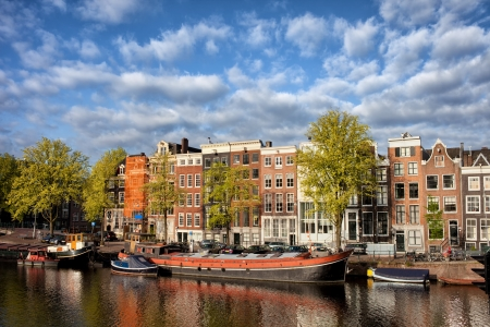 City of Amsterdam picturesque scenery, Dutch style historic houses and boats by the Amstel river waterfront in Netherlands, North Holland province.