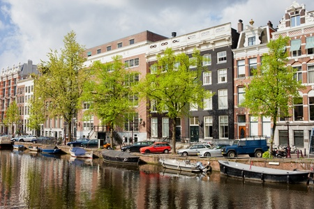 sights: Historic buildings along canal in the city of Amsterdam, Netherlands.