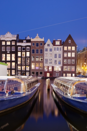 City of Amsterdam historic canal houses at night with passenger tour boats on the first plan, Netherlands, North Holland.