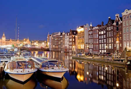 City of Amsterdam in Netherlands at night, historic apartment houses with reflections on water and boats ready for canal tours and cruises. photo