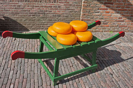 north holland: Wheels of Dutch Gouda cheese on traditional wooden barrow in Amsterdam, Netherlands, North Holland.