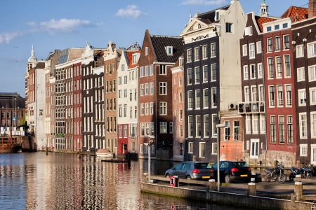 row of houses: City of Amsterdam at sunset, picturesque historical row houses by the canal, North Holland, Netherlands. Stock Photo
