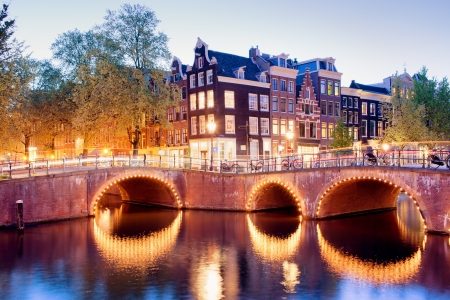 Amsterdam canal bridges illuminated at evening, Netherlands, North Holland province. photo