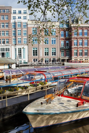 amstel river: Canal cruise boats on the Amstel river in Amsterdam, Netherlands, North Holland province.