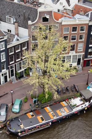 View from above on historic houses and houseboat on a canal in Amsterdam, Netherlands.