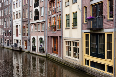 row of houses: Row houses by the canal in Amsterdam, Netherlands, North Holland province. Stock Photo