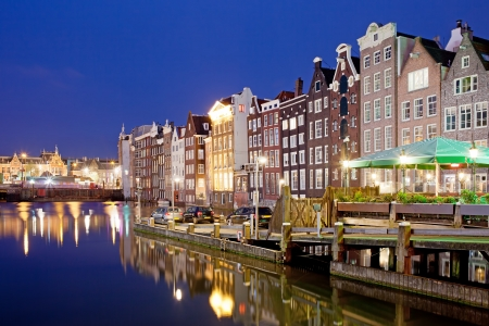 Picturesque city of Amsterdam in Holland, Netherlands at night with historic Dutch style row houses by the canal.