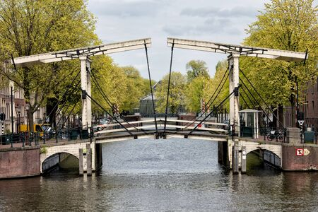 amstel: Bridge on the mouth of Nieuwe Herengracht canal in Amsterdam, Netherlands, on the first plan Amstel river.