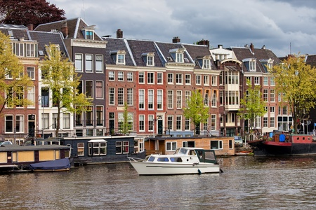 north holland: Amsterdam river view, houses and houseboats on the Amstel river in Netherlands, North Holland province. Stock Photo