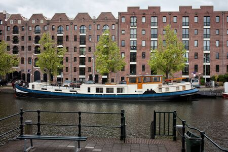 Canal and quayside buildings of Entrepotdok in Amsterdam, converted from old warehouses into apartments, offices, cafes in Holland, Netherlands. Stock Photo - 22505190