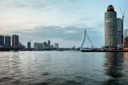 maas: Steely sky and waters of Nieuwe Maas river in Rotterdam, Netherlands, city centre skyline, Erasmus Bridge in the middle.