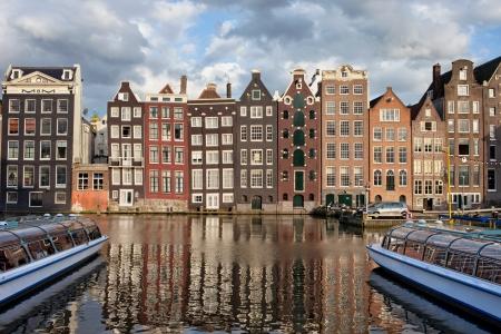 Stad Amsterdam bij zonsondergang in Nederland, terrasvormige Nederlandse stijl historische huizen met reflecties op het water.