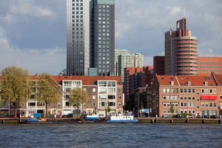 maas: Terraced houses along New Meuse (Dutch: Nieuwe Maas) river and office buildings in the background in Rotterdam city centre, Netherlands.