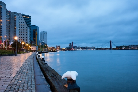 maas: Promenade, apartment blocks and office buildings along Nieuwe Maas (New Meuse) river at twilight in Rotterdam, Netherlands, Willemsbrug at the far end. Stock Photo