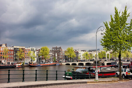 Picturesque cityscape of Amsterdam in the Netherlands, traditional, terraced houses along Amstel river, houseboat barges and Skinny Bridge. photo