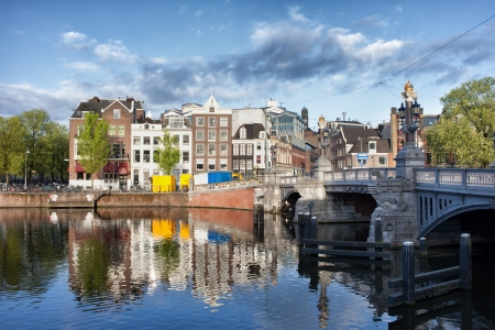 amstel river: Picturesque old houses with reflections on Amstel river waters in the city of Amsterdam, the Netherlands, Blue Bridge (Blauwbrug) on the right.