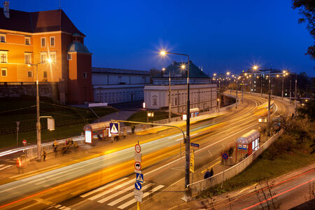 tramline: Night traffic on Solidarity Avenue (Polish: Aleja Solidarnosci), people waiting at bus and tram stops at the Old Town in Warsaw, Poland.