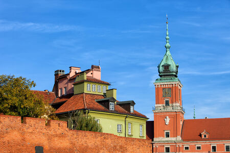 Old Town in Warsaw, Poland. Clock tower of the Royal Castle, houses and fortified brick wall. photo