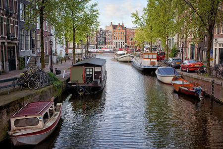 Houseboats, boats and houses along canal in the city of Amsterdam, the Netherlands. photo