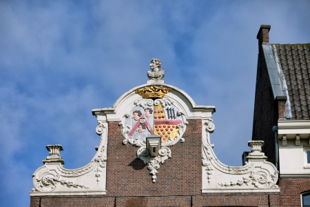 house gable: Ornate Dutch style neck gable with coat of arms on top of a 17th century house in the Old Town of Amsterdam, the Netherlands.