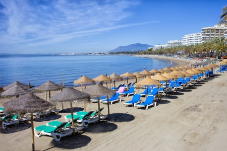 Sun loungers and straw shade umbrellas on a beach by the Mediterranean Sea in Marbella, Costa del Sol, Spain. Stok Fotoğraf