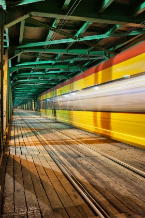 Abstract tram light trail in the lower part of the steel truss Gdanski Bridge in Warsaw, Poland, vanishing point perspective.
