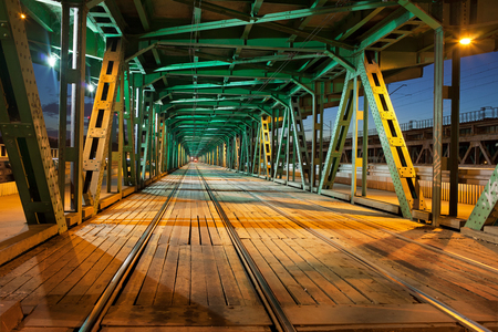Tramway with two tracks in the lower part of the steel truss Gdanski Bridge in Warsaw, Poland, night illumination, vanishing point perspective. photo