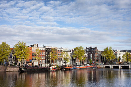 amstel: City of Amsterdam cityscape, terraced houses along Amstel river in Holland, the Netherlands. Stock Photo