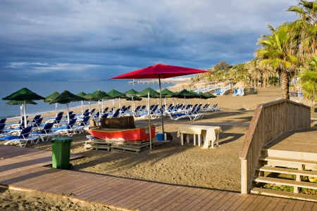 del: Sun loungers with umbrellas on a beach in the morning at popular resort of Marbella in Spain, Costa del Sol, Andalusia region.