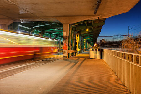 Tram light trail and stop at night in the lower part of the steel truss Gdanski Bridge in Warsaw, Poland. photo