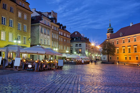 City of Warsaw in the evening, cafes, historic houses and cobbled Castle Square, tranquil urban scenery in the capital of Poland.
