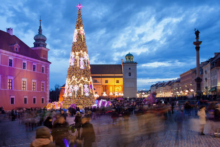 Christmas Tree and people on Castle Square in the Old Town of Warsaw, Poland, illuminated at dusk.