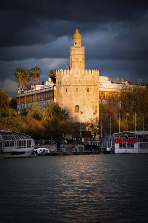 Gold Tower (Spanish: Torre del Oro) of Seville bathed in last rays of the setting sun before the storm, Andalusia region of Spain. photo