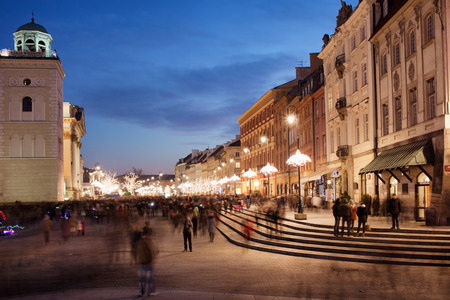 tenement: City of Warsaw in Poland at night, historic tenement houses on Castle Square, part of the Royal Route, bell tower of St. Anne church on the left. Stock Photo