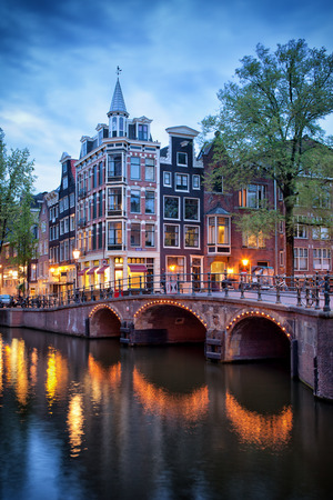 Amsterdam in the evening, old houses and bridge over canal, corner of Grimburgwal and Oudezijds Voorburgwal, North Holland, Netherlands.