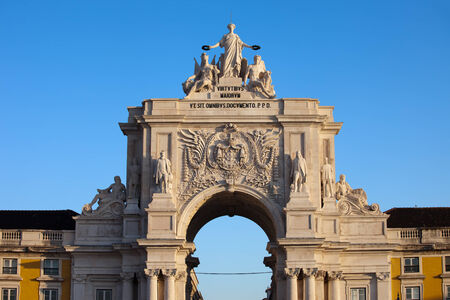 valor: Rua Augusta Arch at sunrise in Lisbon, Portugal. Statues at the top: Allegory of Glory rewarding Valor and Genius, coat of arms of Portugal below.